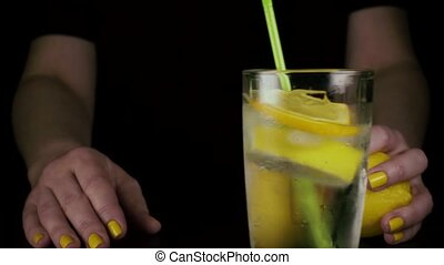 Slow motion. A glass of lemon water rolls on the table