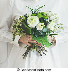 Young woman wearing white clothes holding bouquet. Square...