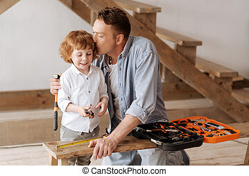 Positive male kid feeling happiness while being with dad -...
