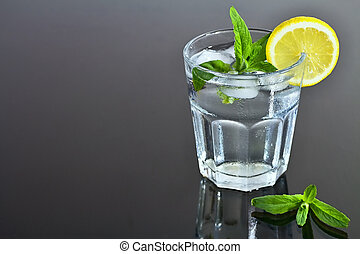 Refreshing glass of water with ice cubes flavored with lemon and mint. Summer refreshment.