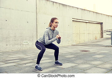 happy woman doing squats and exercising outdoors - fitness,...