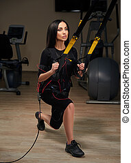 Brunette girl in EMS suit do squat exercise for back with trx suspension