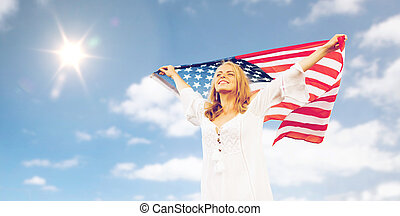 happy young woman with american flag over blue sky