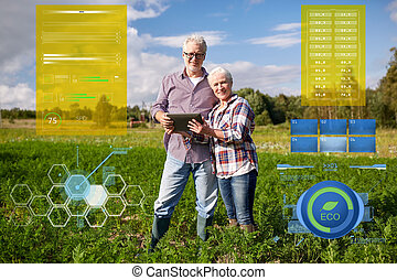 happy senior couple with tablet pc at summer farm - organic...