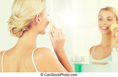 close up of woman washing face with sponge at home - beauty,...