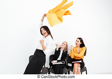 Angry women looking at happy lady colleague. - Image of...