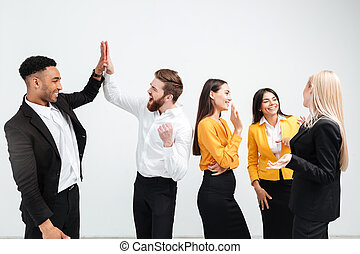 Smiling colleagues business team standing in office gives a high-five