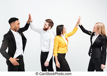 Happy colleagues in office gives a high-five to each other.