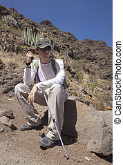 young hiker resting - young hiker sitting on the rock in...