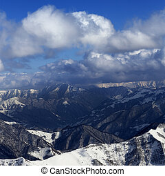 Sunlit winter mountains in clouds, view from off-piste...