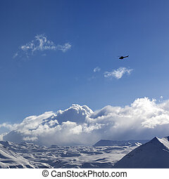 Helicopter above snowy plateau and sunny sky in winter...