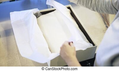 Shop assistant putting a white scarf in a box and with dry flowers