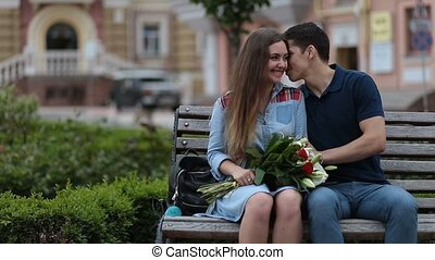Attractive dating couple sitting on bench in park -...
