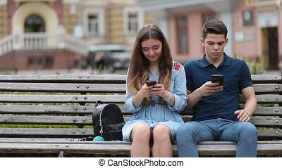 Couple in disinterest moment with phones outdoors - Hipster...