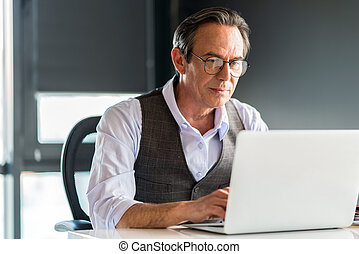 Thoughtful senior businessman typing on notebook -...