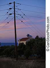 Electricity pole and a house with hot water supply on the...