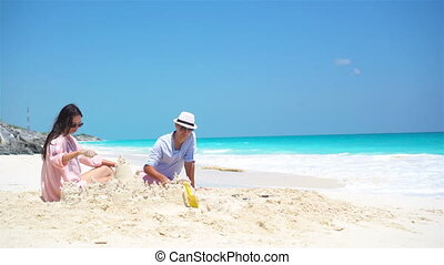 Family of four making sand castle at tropical beach - Family...