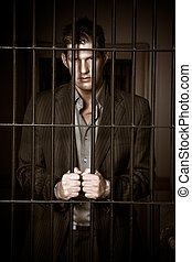 Businessman in jail - A caucasian businessman sitting in...