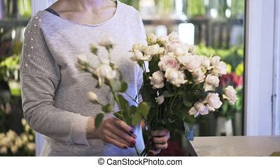 Close up of woman florist arranging roses in a bunch