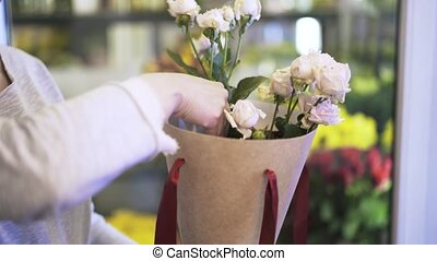 Close up of woman florist hands putting roses in a conical...