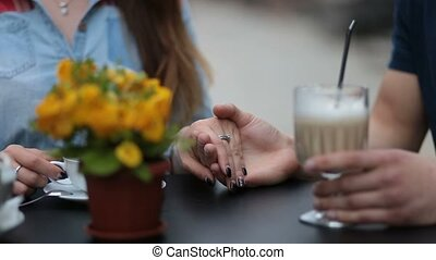 Young couple holding hands at the cafe, closeup