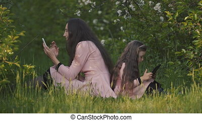 Mom with daughter, tablet and phone in the spring garden