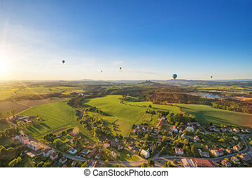 Group of hot air balloons flying above rural countryside of...