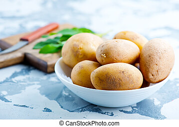 raw potato in bowl and on a table