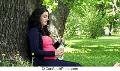 Pregnant woman drinks water from bottle outdoors. Slow...