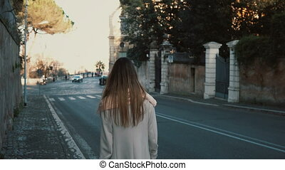 Back view of young lady walking in the city centre alone....
