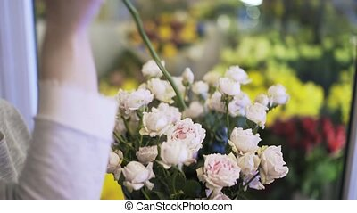 Side view of woman florist hands putting roses in a conical...