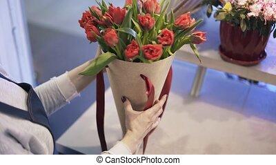 Close up of florist arranging red flowers tilt up