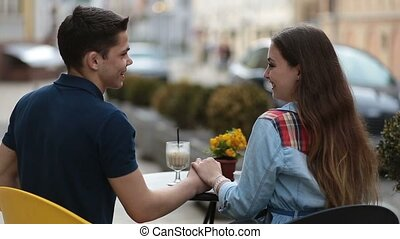 Loving couple sitting at street open-air cafe - Back view of...