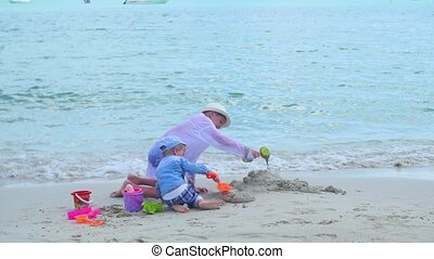 Two children play on a sandy beach with toys. Tropical island, hot day