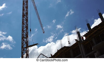 Construction site. Construction crane lifts cargo against the blue sky