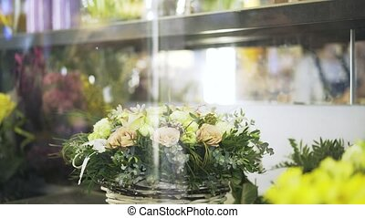 Woman florist arranging flowers in shop window - Close up of...