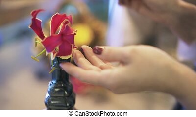 Woman florist putting flowers in a bottle - Close up of a...