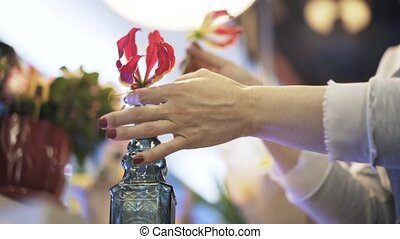 Close up of a woman florist putting flowers in a bottle -...