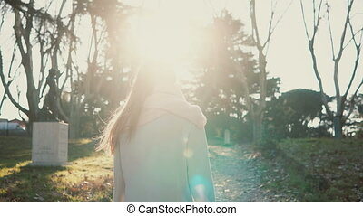 Young beautiful woman walking in the part at bright sunny day. Female turns and smile to somebody, looks happy.