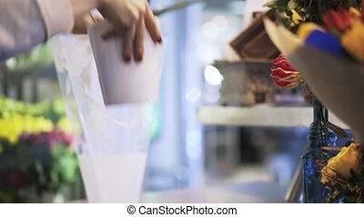 Woman florist putting white flowers in a vase
