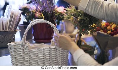 Woman florist putting branches into a basket