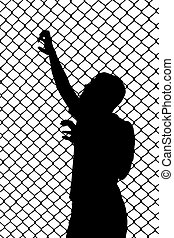 Silhouette of teenager trying to escape from wired enclosure...