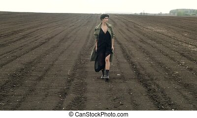 Stylish model posing on field - Woman in black dress and...