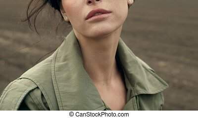 Close-up of woman on field - Close-up portrait of brunette...