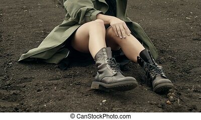 Model in coat posing on ground - Brunette wearing boots and...