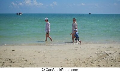 Happy family with children walking on the sandy beach....