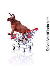 Model cow in shopping cart isolated on white. Shopping for...