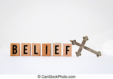 Belief in wooden block letters with silver cross on white...