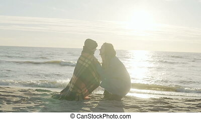 Cute little boy and his young mother spending time together on the shore of the sea. Son kisses woman at sunny beach.