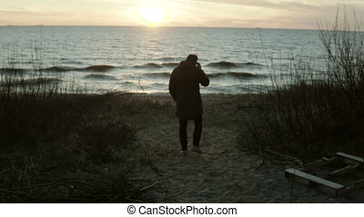 Back view of young man walking on the shore of the sea on sunset. Lonely male spending time alone in beach in cold day.